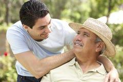 Älterer Mann mit erwachsenem Sohn im Garten Lizenzfreie Stockbilder
