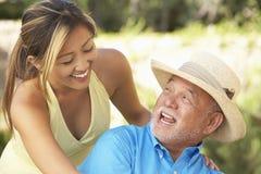Älterer Mann mit erwachsener Tochter im Garten lizenzfreie stockfotos