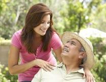 Älterer Mann mit erwachsener Tochter im Garten lizenzfreie stockbilder