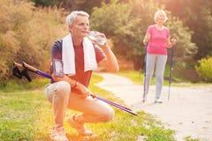 Älterer Mann mit gehendem Trinkwasser des Stocks Lizenzfreies Stockfoto