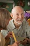 Älterer Mann mit Grußkarte lizenzfreie stockbilder