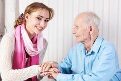 Älterer Mann mit ihrer Pflegekraft zu Hause stockfotografie