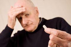 Älterer Mann mit Kopfschmerzenholdingtablette oder -pille Stockfotografie