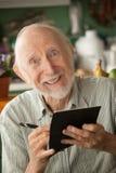 Älterer Mann mit Scheckheft lizenzfreie stockfotos