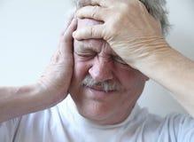 Älterer Mann mit schrecklichen Kopfschmerzen Stockbilder