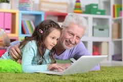 Älterer Mann mit seiner Enkelin, die Laptop verwendet Stockfotografie