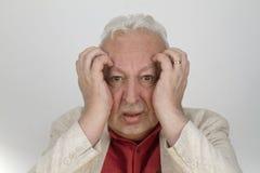 Älterer Mann mit starken Kopfschmerzen lizenzfreie stockfotos