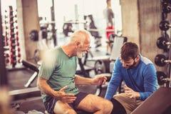 Älterer Mann mit Trainer lizenzfreies stockbild
