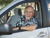 Älterer Mann am Rad des Autos Stockfotos