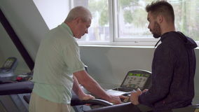 Älterer Mann schaltet die Tretmühle ein stock footage