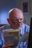 Älterer Mann schaut besorgt und umgekippt, während er die Lohnlisten, die on-line sind, vertikal Lizenzfreie Stockfotos