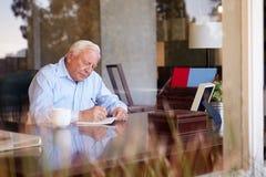 Älterer Mann-Schreibens-Abhandlungen im Buch, das am Schreibtisch sitzt Stockbild