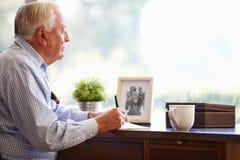 Älterer Mann-Schreibens-Abhandlungen im Buch, das am Schreibtisch sitzt Stockfotos