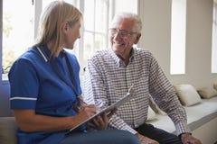 Älterer Mann sitzt mit der Krankenschwester, die Anmerkungen am Ruhesitz macht lizenzfreie stockfotografie