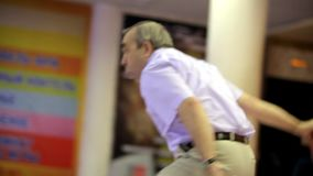 Älterer Mann spielt Bowlingspiel stock video