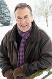Älterer Mann-stehende Außenseite in der Schnee-Landschaft Lizenzfreies Stockbild