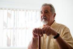 Älterer Mann Thougtful, der beim Halten des gehenden Stocks weg schaut Lizenzfreie Stockfotos