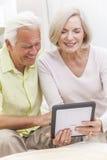Älterer Mann-u. Frauen-Paare unter Verwendung des Tablette-Computers Stockfoto