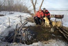 Älterer Mann und Frau, die mit einem Hund betrachtet das Feuer sitzt Lizenzfreie Stockfotografie