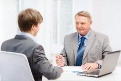 Älterer Mann und junger Mann, der Sitzung im Büro hat Stockbilder