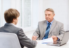 Älterer Mann und junger Mann, der Sitzung im Büro hat Lizenzfreie Stockbilder