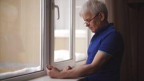 Älterer Mann unter Verwendung des Telefons Älterer Mann, der durch die Fotos im Smartphone leicht schlägt stock footage
