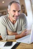 Älterer Mann updatind Zeitplan zu Hause Stockbilder