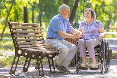 Älterer Mann verstärkt seine Frau im Rollstuhl Stockfotografie