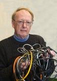 Älterer Mann verwirrt durch verwirrte Drähte Stockfoto