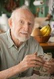 Älterer Mann zu Hause, der Geld zählt stockfotografie