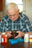 Älterer Mannesverbrauchtes Geld auf Medizin Lizenzfreie Stockbilder