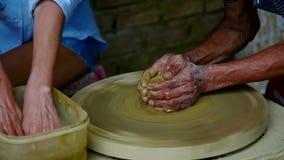 Älterer Meister zeigt das Mädchen, das Tongefäß auf Töpferrad herstellt stock video