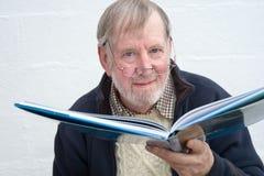 Älterer mit großem Buch. Stockbild