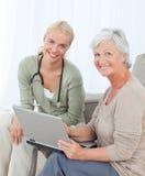 Älterer mit ihrem Doktor, der an dem Laptop arbeitet Stockfotos