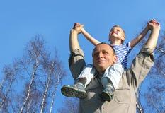 Älterer mit Kind auf Schultern vor Birke Stockfoto