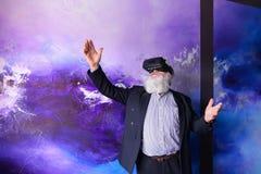 Älterer moderner Mann, der VR-Gläser unterhalten verwendet und heraus hängt Stockbilder