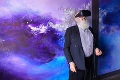 Älterer moderner Mann, der VR-Gläser unterhalten verwendet und heraus hängt Lizenzfreies Stockfoto