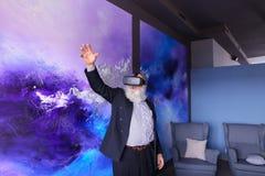 Älterer moderner Mann, der VR-Gläser unterhalten verwendet und heraus hängt Lizenzfreie Stockfotos