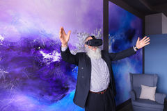 Älterer moderner Mann, der VR-Gläser unterhalten verwendet und heraus hängt Stockfotografie