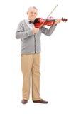 Älterer Musiker, der eine Violine mit einem Stab spielt Stockbild