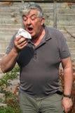 Älterer niesender Mann. Stockbilder