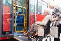 Älterer Paar-Einstieg-Bus unter Verwendung der Rollstuhl-Zufahrtsrampe Stockbilder