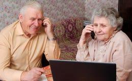 Älterer Paarklatsch über etwas durch Telefon Stockfotografie
