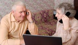 Älterer Paarklatsch über etwas durch Telefon Stockbilder