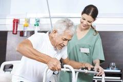 Älterer Patient, der von der weiblichen Krankenschwester In Using Walker unterstützt wird stockfotos