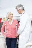 Älterer Patient, der von Doktor With Crutches unterstützt wird lizenzfreies stockbild