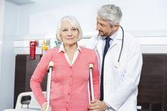Älterer Patient, der von reifem Doktor With Crutches unterstützt wird stockfotografie