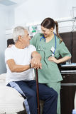 Älterer Patient und Junge-Krankenschwester Looking At Each anderes Stockbilder