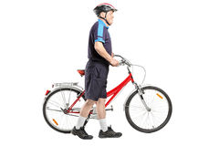 Älterer Radfahrer, der ein Fahrrad drückt Stockfotos