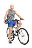 Älterer Radfahrer, der einen Blauhelm gesetzt auf seinem Fahrrad hält Lizenzfreies Stockbild